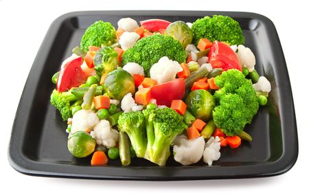 Vegetables: cauliflower, brussels sprouts, broccoli, carrots, string beans  and tomatoes on plate photo