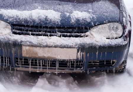 Frozen car covered with snow and ice photo