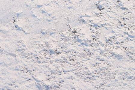 emphasizes: Texture of the snow. Thin snow crust on the surface of the frozen lake. Natural sunlight emphasizes texture. Pattern # 4 Stock Photo