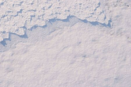 emphasizes: Texture of the snow. Thin snow crust on the surface of the frozen lake. Natural sunlight emphasizes texture. Pattern # 5 Stock Photo