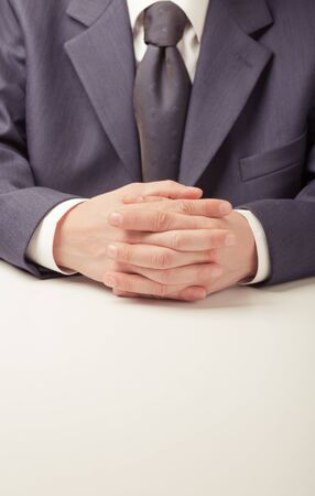 handbreadth: Man in business suit sitting at the table Stock Photo