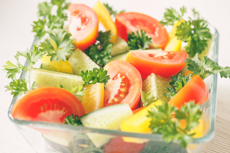 viands: Fresh vegetables with greens in a transparent bowl on a light background Stock Photo