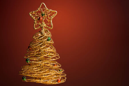Golden sparkling Christmas tree on dark red background photo