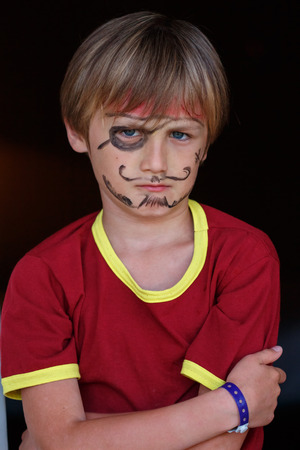 medium closeup: A close-up portrait of a grumpy angry pirate boy Stock Photo