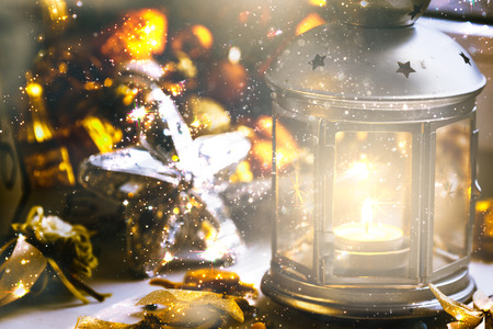 nativity set: Christmas still life: lantern with burning candle and New Year tree decorations. Shallow depth of field
