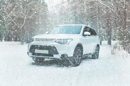 De moderne SUV op een achtergrond van een winters bos. Offroad auto op de sneeuw