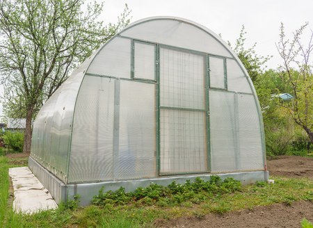 garth: A small greenhouse with air vents in the garden