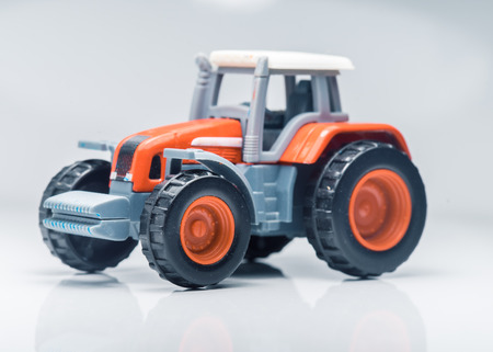 harrowing: Small red toy tractor on light background, shallow depth of field
