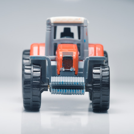 torque: Small red toy tractor on light background, shallow depth of field