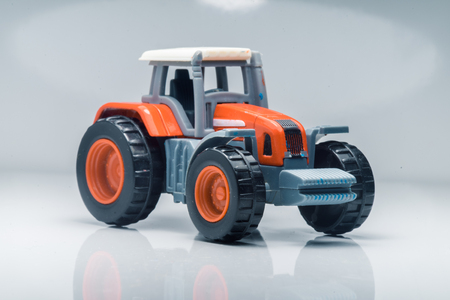 tractive: Small red toy tractor on light background, shallow depth of field