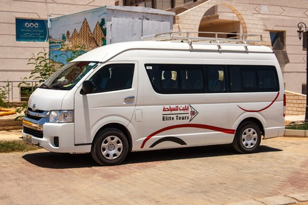 panel van: EGYPT, SHARM EL SHEIKH - JULY 20, 2015: Sharm el-Sheikh is holiday resort and significant centre for tourism in Egypt. White commercial passenger mini bus waiting for tourists