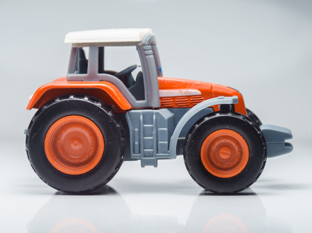agriculture machinery: Closeup Of Small Red Agricultural Toy Tractor, Icon Farmer Machinery,  Agriculture Business Concept.