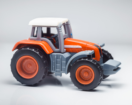 Closeup Of Small Red Agricultural Toy Tractor, Icon Farmer Machinery,  Agriculture Business Concept.