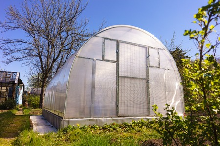 Modern Polycarbonate Greenhouse in Allotments for Growing Vegetables, Glasshouse Made of Polycarbonate, Farmland with Glasshouse, Plant Nursery, Sunlight Semicircle Hothouse, Self-sustaining Stock Photo