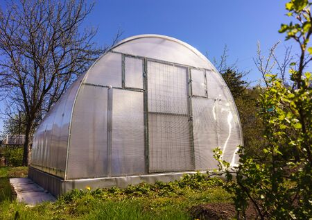 hothouse: Modern Polycarbonate Greenhouse in Allotments for Growing Vegetables, Glasshouse Made of Polycarbonate, Farmland with Glasshouse, Plant Nursery, Sunlight Semicircle Hothouse, Self-sustaining Stock Photo