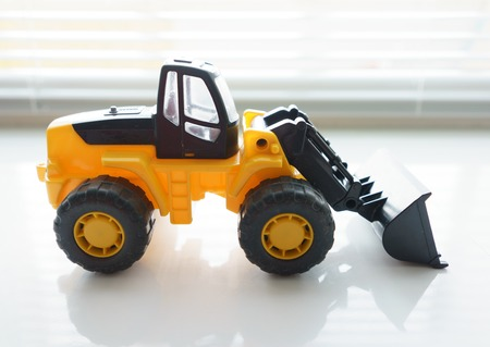 earthmover: Toy Industrial Vehicle, Plastic Wheel Loader Excavator for Earth Moving Works at Construction Site, Miniature Earth Mover, Backhoe Loader, Frontend Loader with a Big Scoop, Heavy-duty Bulldozer Stock Photo