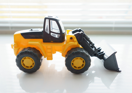 Toy Industrial Vehicle, Plastic Wheel Loader Excavator for Earth Moving Works at Construction Site, Miniature Earth Mover, Backhoe Loader, Frontend Loader with a Big Scoop, Heavy-duty Bulldozer Stock Photo