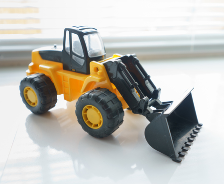 cargador frontal: Vehículo de juguete industrial, la rueda de plastico cargador de excavador por un movimiento de tierras Trabajos de construcción, miniatura motor de la tierra, retroexcavadora, Frontend Loader con un gran Pala, niveladora de servicio pesado Foto de archivo