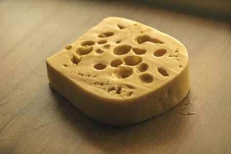 Dutch Hard Cheese Maasdam or Emmentaler Slice Porous Yellow , Cheese with Holes, Swiss Cheese Block Closeup