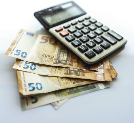 Banconote e calcolatrice, banconote in euro su sfondo bianco, denaro, finanza, tasse, profitti e costi, 50 euro, banconote in euro, calcolo del tasso di interesse composto o concetti aziendali di investimento finanziario
