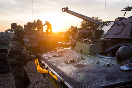 legion: Tankers of the foreign Legion on the teachings. Black Legionnaire inspects tank. The South Of France. Stock Photo