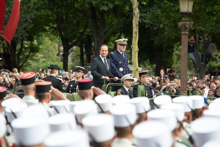 Paris. France. July 14, 2012. French President Francois Hollande welcomes servicemen and citizens from the car during the parade on the Champs Elysees in Paris.