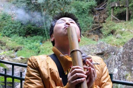 hombre fumando: Hombre que fuma marijuanas asi�ticos