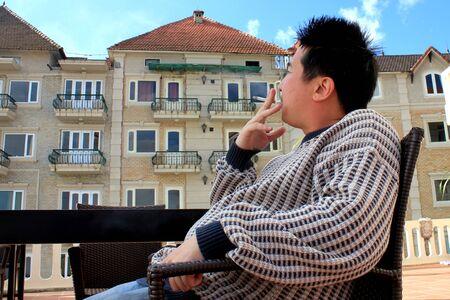 hombre fumando: Hombre asi�tico fumar fuera del edificio