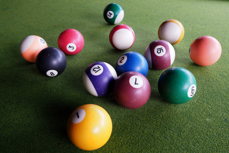 The colourful pool ball on the green background