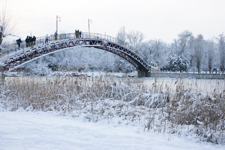 People cross the river on a bridge in the winter.