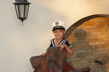 Boy child in captains clothes smiles tenderly Stock Photo
