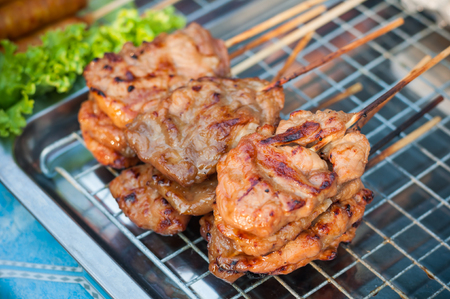 Close up Grilled Pork stick on grid  market, Thai cuisine traditional signature street food, quick delicious and easy eating