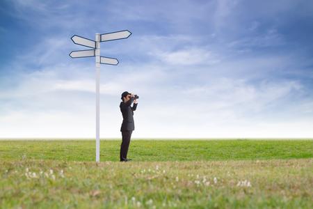 Businessman using binoculars looking direction. Stock Photo