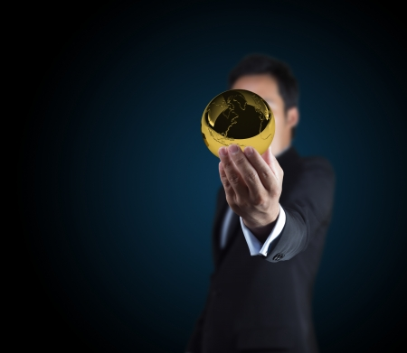 Businessman holding the gold globe on the hands. photo
