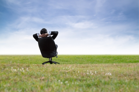 Man relaxing on chair in green meadow.