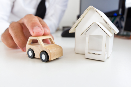 Businessman holding a wooden car on a table. Stock Photo