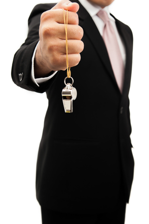 Businessman holding a silver whistle.