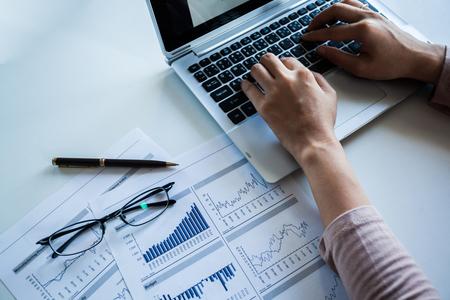 チェックのビジネスマンは、紙、ノート パソコンに利益を報告しました。