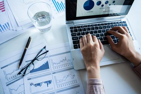 Zakenman het controleren van gemelde winst op het papier en laptop.