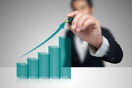 capital: Businessman with growth chart of profits. Stock Photo