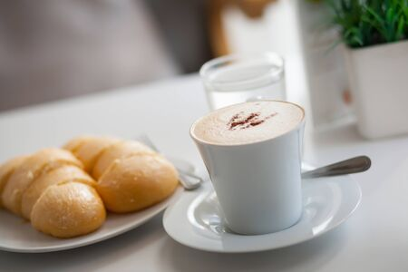 Hot coffee and bread on table.