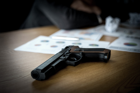gun and us dollar bill on office desk
