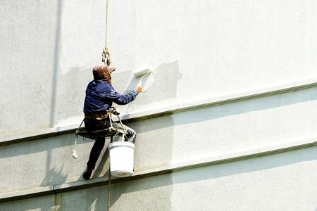 Maler, der an weißem Gebäude hängt Standard-Bild
