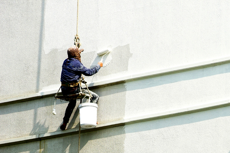 painter hanging on white building Foto de archivo
