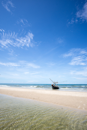 Fishing boat on a beach and deep bluesky background , landscape Thailand