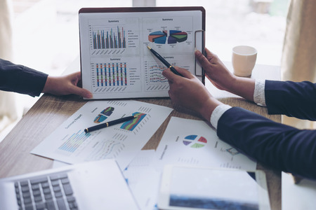 financial Image of two young business people pointing at business document during discussion at meeting , Notebook on wood table
