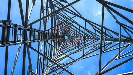 Telephone pole technology mobile telephone network base station telecommunication tower on blue sky background - bottom view Stock Photo