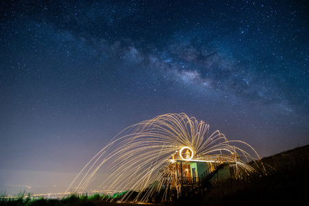 night landscape mountain and Wield the fire , milkyway galaxy background , long exposure ,low light Stock Photo