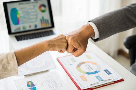close up hand of business partnerships people bump hands finishing up meeting showing unity over office desk , business teamwork concept Stock Photo