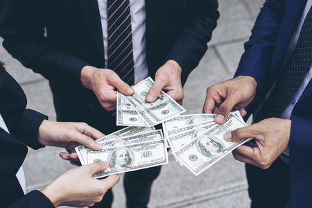 business person  holding money US dollar bills in hand , concept for success business